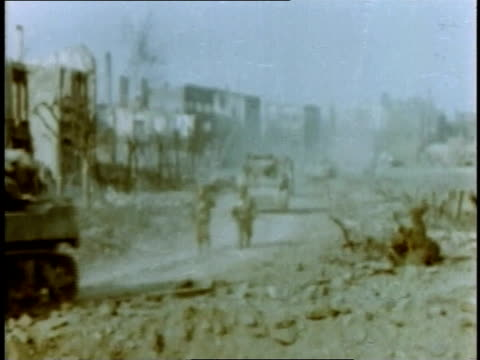 march 1945 montage tanks, followed by soldiers, driving through rubble-filled streets of destroyed town / germany - rubble stock-videos und b-roll-filmmaterial