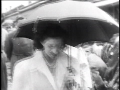 march 20, 1947 montage men and women with umbrellas walk past a large group of children / georgia, united states - anno 1947 video stock e b–roll