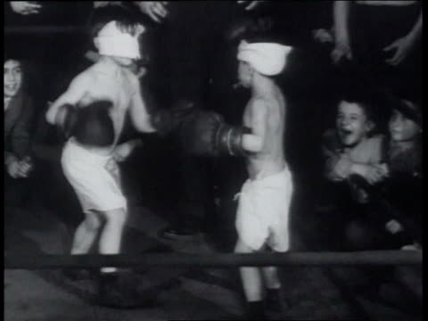 vidéos et rushes de march 22 1939 ws two blindfolded boys boxing in ring man coming in to adjust one blindfold and leaving / new york city new york united states - caméra tremblante