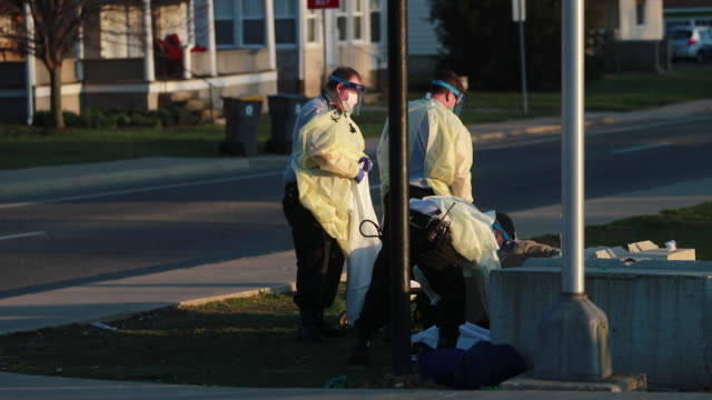 first responders from iu health bloomington hospital pick up a woman at the corner of 1st st and s walnut st who was sitting slumped over and was... - ecke eines objekts stock-videos und b-roll-filmmaterial