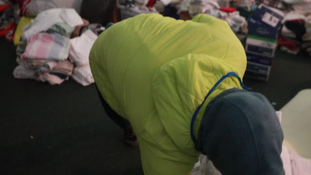 march 24, 2020 - bloomington, indiana usa: a volunteer sorts items donated from the community at an emergency isolation shelter for people... - volunteer stock-videos und b-roll-filmmaterial