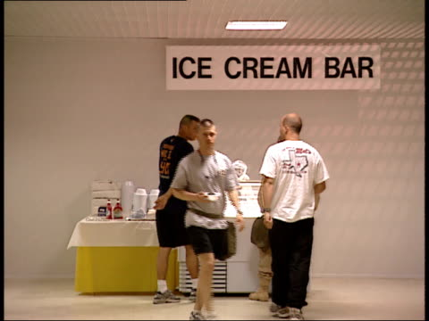 march 31, 1999 montage u.s. army soldiers being served at ice cream bar and eating in the mess hall at as saliyah army base / doha, qatar - camp as sayliyah bildbanksvideor och videomaterial från bakom kulisserna