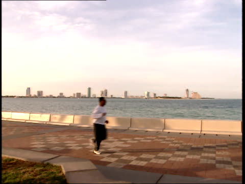 March 31 1999 WS Pedestrians walking and jogging along seaside boulevard with city skyline across the sea in the distance / Doha Qatar