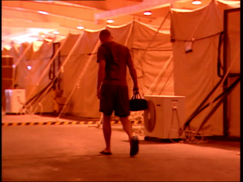 March 31 1999 TS Soldier in shorts and shirt walking through interior of tented area / Doha Qatar