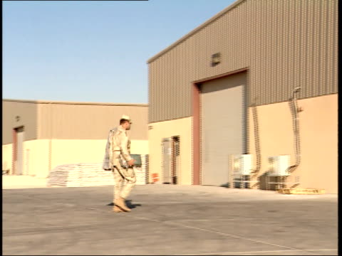 March 31 1999 TS US Army soldier walking across As Saliyah Army Base and entering metal building / Doha Qatar