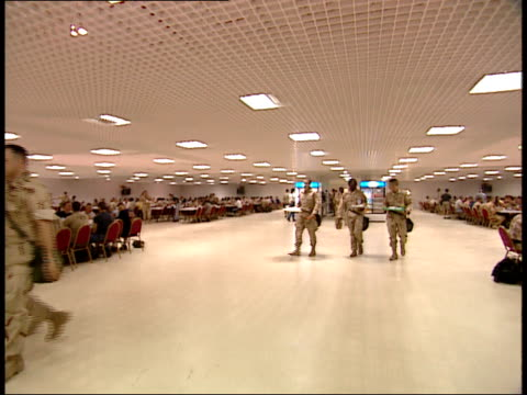 March 31 1999 PAN US Army soldiers walking through cafeteria while carrying food trays As Saliyah Army Base / Doha Qatar