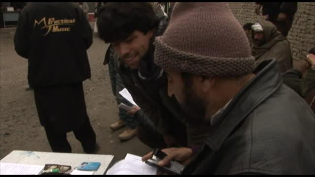 march 4 2005 zi official standing at table holding a clipboard and taking fingerprints / kabul afghanistan - bordsyteinspelning bildbanksvideor och videomaterial från bakom kulisserna