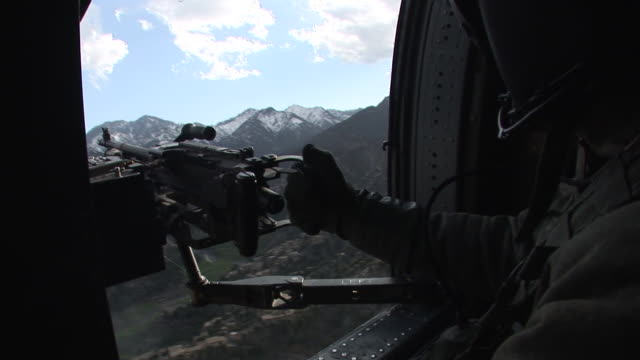 march 5 2009 aerial us army helicopter taking off and flying over mountainous terrain with soldier manning mounted machine gun / kunar afghanistan - korengal valley stock videos & royalty-free footage
