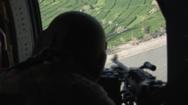 march 5 2009 aerial us army soldier manning a machine gun in flying helicopter on patrol / kunar afghanistan - afghanistan stock videos & royalty-free footage