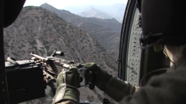 march 5 2009 aerial us army soldier manning machine gun in helicopter / kunar afghanistan - korengal valley stock videos & royalty-free footage