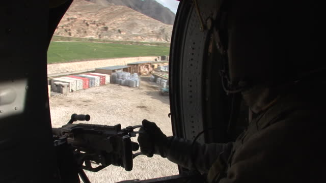 march 5 2009 aerial us army soldier manning machine gun in helicopter during take off / kunar afghanistan - korengal valley stock videos & royalty-free footage