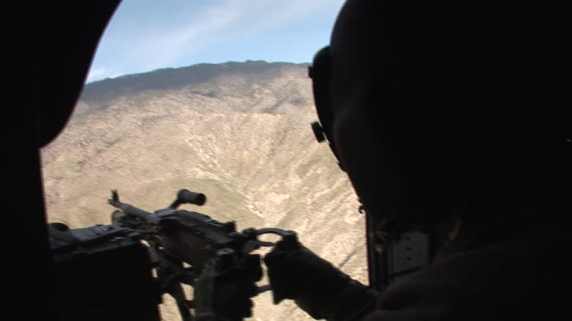 vídeos y material grabado en eventos de stock de march 5 2009 aerial us army soldier manning machine gun within helicopter flying over mountainous terrain of the korengal valley / kunar afghanistan - korengal tal