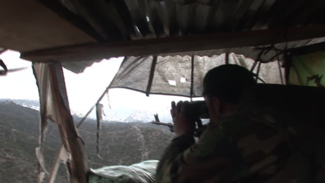 march 5 2009 montage afghan national army soldier peering through binoculars inside camouflaged position overlooking village on rocky hillside /... - korengal valley stock videos & royalty-free footage