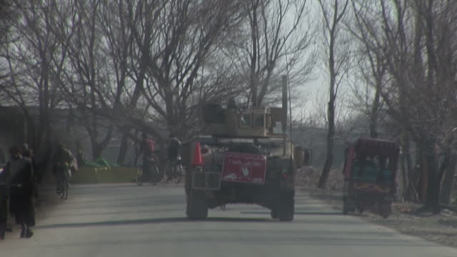 march 5, 2009 u.s. army armored vehicles in convoy driving past line of bicyclists / bagram, afghanistan - bagram stock videos & royalty-free footage