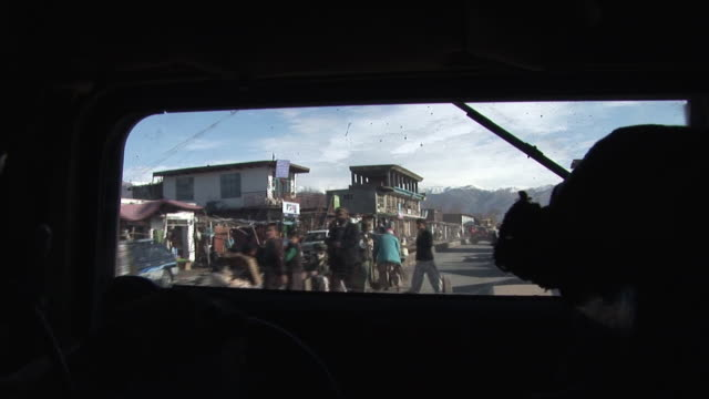vídeos de stock, filmes e b-roll de march 5 2009 pov us army armored vehicles in convoy driving through village on bumpy road / bagram afghanistan - interior de carro