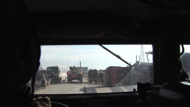 March 5 2009 POV US Army armored vehicles in convoy driving through village with soldiers talking / Bagram Afghanistan