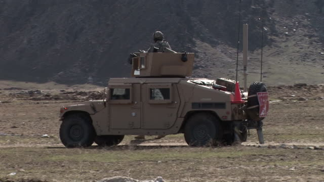 march 5 2009 ts us army light armored vehicle and soldiers on foot advancing across a field / bagram afghanistan - bagram video stock e b–roll