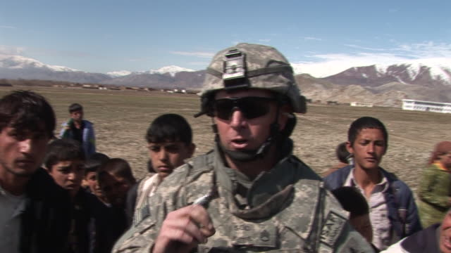 stockvideo's en b-roll-footage met march 5 2009 cu us army soldier being interviewed by a reporter about teaching village children the english language / bagram afghanistan - bagram