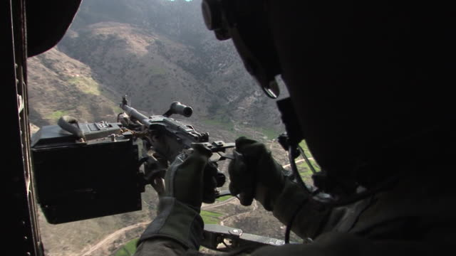 march 5 2009 zi us army soldier manning a machine gun within helicopter flying over the korengal valley / kunar afghanistan - afghanistan stock videos & royalty-free footage
