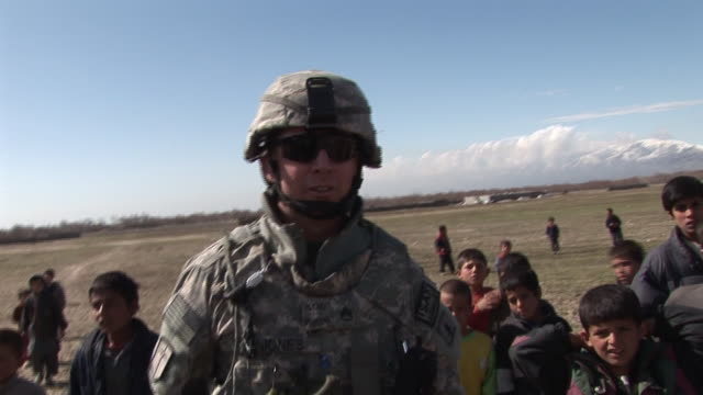 march 5, 2009 u.s. army soldiers talking and playing with a group of village children / bagram, afghanistan - bagram stock videos & royalty-free footage