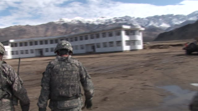 stockvideo's en b-roll-footage met march 5 2009 pov us army soldiers walking on dirt road near armored vehicles and large white building / bagram afghanistan asia - bagram