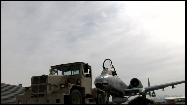 march 6, 2009 tractor towing a u.s. air force fighter jet / bagram, afghanistan - bagram air base stock-videos und b-roll-filmmaterial