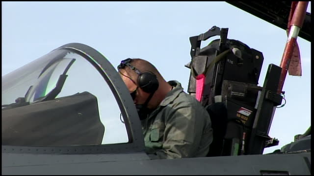 march 6 2009 ms us air force airman wearing headphones in cockpit of fighter jet preparing for takeoff / bagram afghanistan - bagram video stock e b–roll