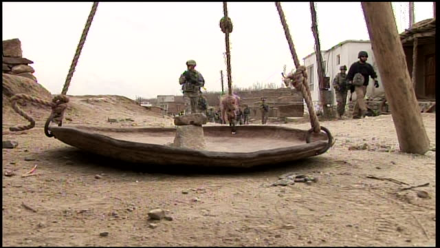 March 6 2009 LA US Army and Afghan soldiers patrolling past tripod in village / Afghanistan