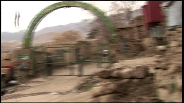 march 6 2009 pan us army and afghan soldiers walking past iron fence in village / afghanistan - 門点の映像素材/bロール
