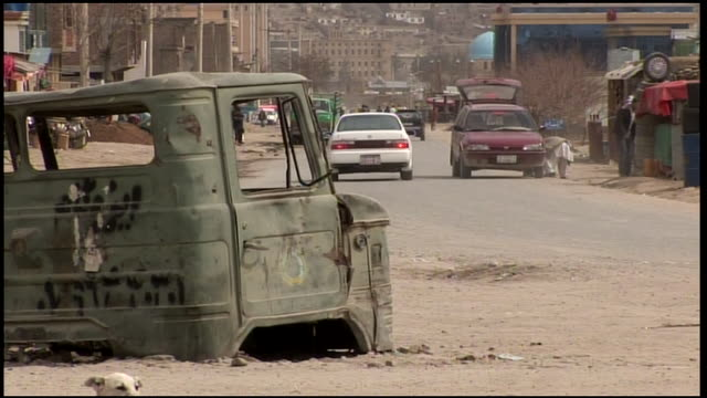 march 9 2009 ws motorcycle driving on a dusty street with a junk car body in the foreground / kandahar afghanistan - kandahar afghanistan stock videos & royalty-free footage