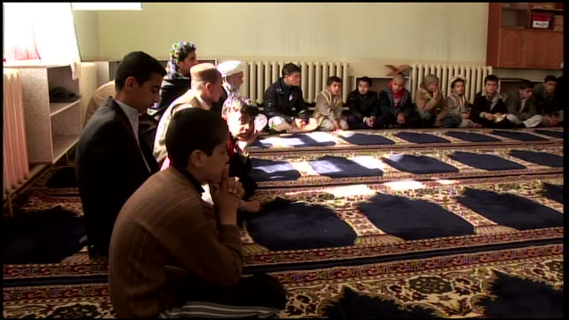 march 9 2009 pan worshipers of all ages settling in to pray at mosque / kandahar afghanistan - auf dem boden sitzen stock-videos und b-roll-filmmaterial