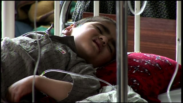 march 9 2009 ms young patient in hospital bed hooked up to intravenous drip / kandahar afghanistan - ein männliches baby allein stock-videos und b-roll-filmmaterial