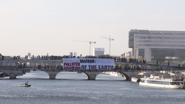 vidéos et rushes de march for the climate: anti-macron streamers deployed on paris bridges. simone de beauvoir footbridge - lieux géographiques