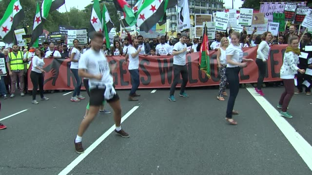 march in support of refugees **music heard sot** protesters with giant banner and syrian flags / demonstrators dancing in front of march then... - music stand stock videos and b-roll footage