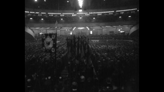marchers bearing german flags parade down center aisle of the sportpalast at a hindenburg rally passing a huge audience / rally spectators / note... - 1932 stock videos & royalty-free footage
