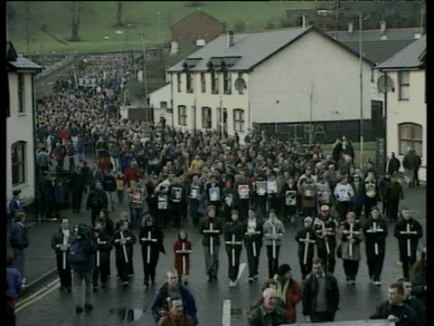 Marchers carrying crosses and photographs of victims follow route of original civil rights march on 26th anniversary of Bloody Sunday shootings...