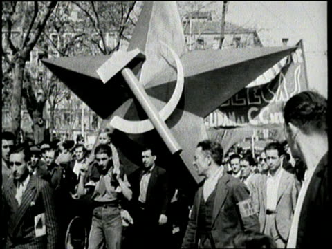 marchers in a parade carry emblems and icons of communism including a large banner of joseph stalin's face - 1936 stock-videos und b-roll-filmmaterial