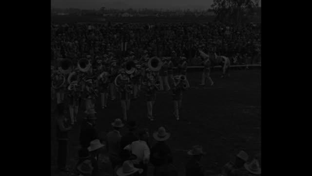 marching band at rodeo / several views of cowboys bucking broncos and steer wrestling / several officials stand nearby as bronco and rider appear to... - bocksprång bildbanksvideor och videomaterial från bakom kulisserna