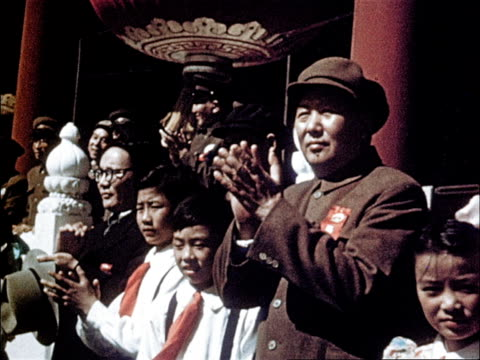 Marching band dressed in white and carrying large flags / parade is ending as students clap and wave flowers at Chairman Mao