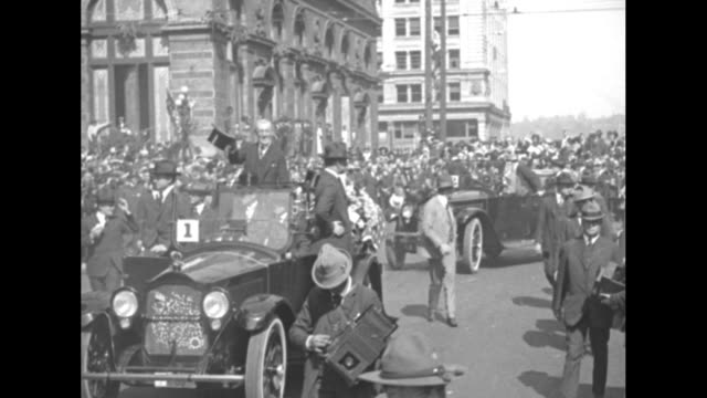 A marching band in lightcolored uniforms walks from the camera / Pres Woodrow Wilson stands in the rear of a convertible car waving his hat First...