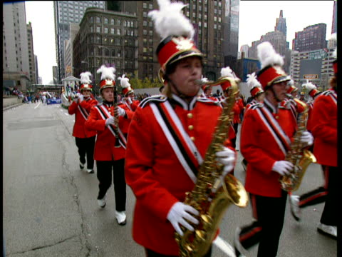 marching band in red uniforms march past camera playing flutes trumpets saxophones clarinets and tuba - saxophone stock videos and b-roll footage