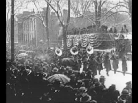 marching band passes grandstand during parade celebrating inauguration of new york governor franklin d roosevelt crowds along street watch some with... - 長点の映像素材/bロール