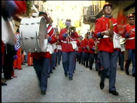 ms la marching band walking  and playing music on city street / ivrea, torino, italy / audio - banda che marcia video stock e b–roll