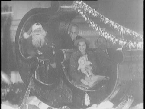 vidéos et rushes de marching band walks down the street during hollywood christmas parade / edgar bergen and charlie mccarthy ride down the street on a float as they... - ventriloque