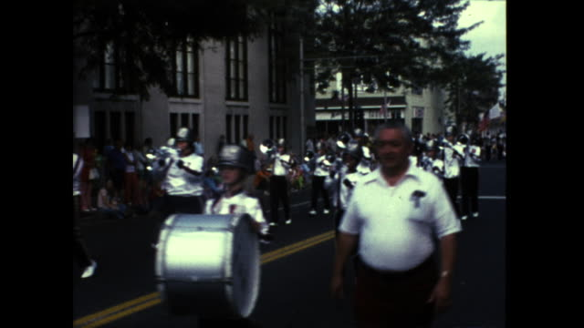 marching band with lots of drums dressed in white and silver uniform marching down the street buildings in the background - 道路名の標識点の映像素材/bロール