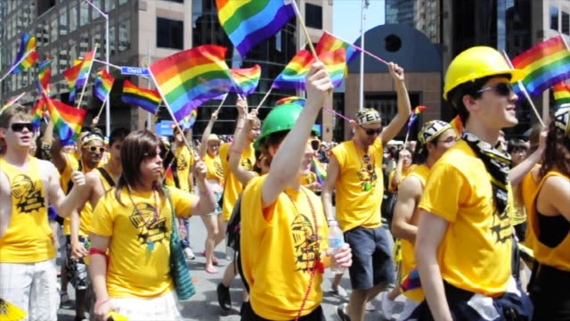 Marching people wearing yellow tshirts and waving rainbow flags The traditional gay pride parade happens every Summer in the important Canadian city