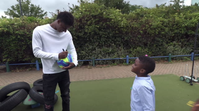 marcus rashford playing football with children on a council estate - autographing stock videos & royalty-free footage