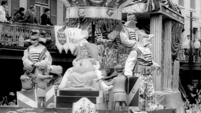 stockvideo's en b-roll-footage met mardi gras floats going down the street with a king and mythology theme apparent / people carrying flaming torches walking in parade / huge crowd and... - 1965