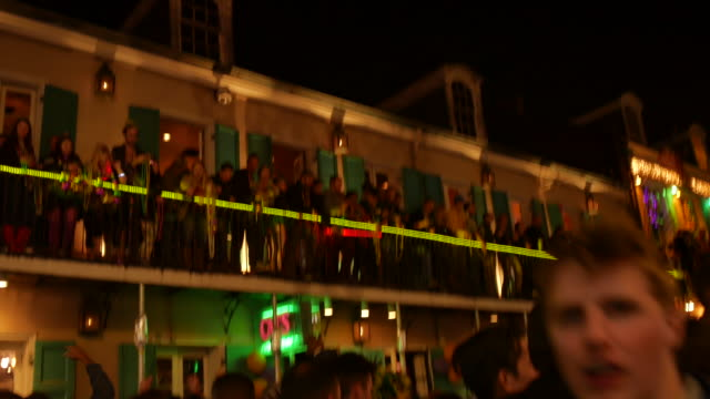 Mardi Gras revelers pack a balcony on Bourbon Street to throw beads at passing pedestrians below during Mardi Gras