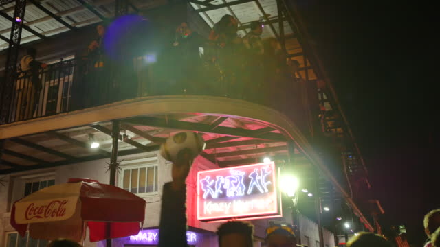 Mardi Gras revelers pack balconies at Krazy Korner on Bourbon Street with the street below also packed with celebrants partying during Mardi Gras